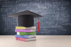 Education concept. Abstract graduation hat and colorful book pile placed on wooden surface. Chalkboard with mathematical formulas in the background. Education Stock Image