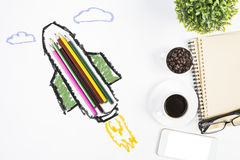 Education concept. Abstract rocket ship sketch around colorful pencils on white desktop with coffee cup, glasses, smartphone and other items. Education concept stock photo