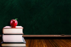 Education Concept With Apple on Books and Blackboard Background Stock Photos