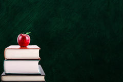 Education Concept With Apple on Books and Chalkboard Background Royalty Free Stock Photos