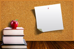 Education Concept With Apple on Books and Corkboard Background Stock Images