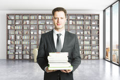 Education concept. With attractive businessman holding pile of books in library interior. 3D Rendering Royalty Free Stock Photo