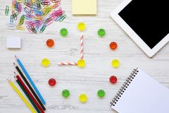 Education concept, back to school. Nine hours on watch. Clock made of colorful sweet candies, accessories for study over white woo. Den background, from above stock photos