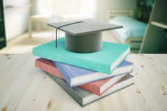 Education concept bedroom. Books and graduation cap on wooden desktop and blurry bedroom in the background. Education concept. 3D Rendering Royalty Free Stock Photo
