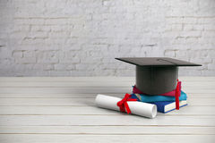 Education concept. Black mortarboard, books and diploma placed on wooden surface and brick wall background. Education concept. 3D Rendering Stock Images