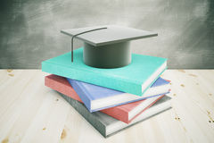Education concept books and cap. Books and graduation cap on wooden desktop with chalkboard in the background. Education concept. 3D Rendering Stock Photography