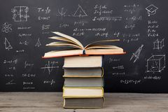Education concept - books on the desk in the auditorium. Formulas on the blackboard royalty free stock photo