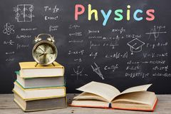 Education concept - books on the desk in the auditorium. Formulas and Physics inscription on the blackboard royalty free stock photo