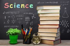 Education concept - books on the desk in the auditorium. Formulas and science inscription on the blackboard stock image