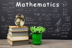 Education concept - books on the desk in the auditorium. Formulas and Mathematics inscription on the blackboard royalty free stock image