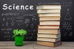 Education concept - books on the desk in the auditorium. Formulas and science inscription on the blackboard royalty free stock photography