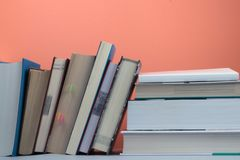 Education concept. Bookshelf with important books on coral background royalty free stock photo