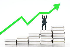 Education concept businessman with arrow. Education concept with businessman standing on book stairway and upholding green chart arrow on light background. 3D Royalty Free Stock Photos
