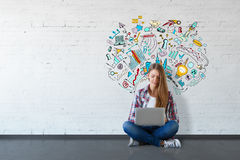 Education concept. Cheerful young woman sitting on floor and using laptop in white brick interior with business sketch on wall. Education concept. 3D Rendering royalty free stock photography