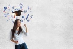 Education concept. Cheerful young woman standing on concrete wall background with mortarboard and educational sketch. Education concept Royalty Free Stock Photo