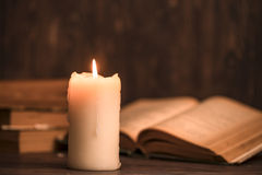 Education concept. Close-up view of old burning candle with shab. By old book on wooden background. Focus on the candle Stock Photos