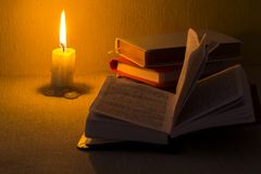 Education concept. Close-up view of old burning candle with shabby old book on table background. Focus on the candle.  Royalty Free Stock Photography