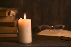 Education concept. Close-up view of old burning candle. With shabby old book on wooden background. Focus on the candle Stock Images