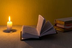 Education concept. Close-up view of old burning candle with shabby old book on table background. Focus on the candle.  Stock Photos