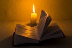 Education concept. Close-up view of old burning candle with shabby old book on table background. Focus on the candle.  Stock Image