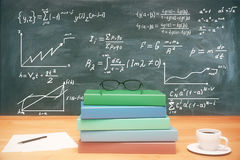 Education concept. Closeup of wooden desk with pile of books, coffee cup, glasses and other items on chalkboard with mathematical formulas background. Education Stock Photo