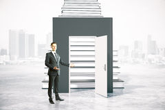 Education concept entrance invitation. Education concept with businessman inviting to enter through an open door leading to book ladder. 3D Rendering Stock Photography