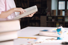 Education concept. Girl reading a book in library of school. Royalty Free Stock Photography