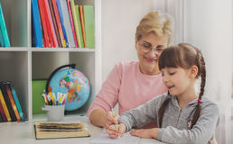 Education concept, grandmother reading a book for grandchildren Stock Photos