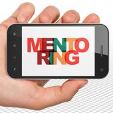 Education concept: Hand Holding Smartphone with Mentoring on  display Stock Photography