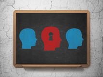 Education concept: head with keyhole icon on. Education concept: row of Painted blue head icons around red head with keyhole icon on School Board background, 3d Royalty Free Stock Images