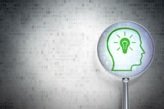 Education concept:  Head With Lightbulb with optical glass on di Royalty Free Stock Image