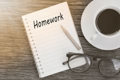 Education concept. Homework word on notebook with glasses, pencil and coffee cup on wooden table. stock images