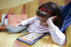 education concept. Little girl lying on the sofa at home studying home work on the tablet royalty free stock photo