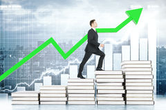 Education concept man climbing stairs. Education concept with businessman climbing book stairway with business chart and green arrow in the background. 3D Stock Photography