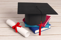 Education concept. Mortarboard, books and paper roll on wooden surface. Education concept. 3D Rendering Stock Photo