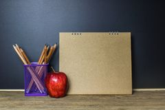 Education concept. Pencil and red apple on wood table. Education concept. Pencil and red apple on wood table with brown blank calendar with blackboard Royalty Free Stock Photo