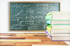 Education concept. Pile of colorful books on wooden surface and blackboard with mathematical formulas. 3D Rendering Royalty Free Stock Image