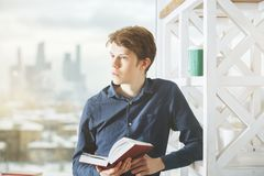 Education concept. Portrait of handsome young man reading book in office with shelf and window with blurry city view. Education concept Stock Photography
