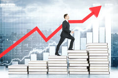 Education concept red arrow. Education concept with businessman climbing book stairway with business chart and red arrow in the background. 3D Rendering Stock Photo
