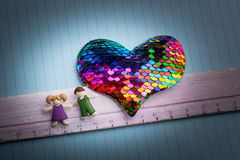 Education concept by ruler and heart beside two kids stock photography
