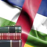 Education concept - Stack of books and reading glasses against National flag of Central African Republic royalty free stock photography