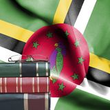 Education concept - Stack of books and reading glasses against National flag of Dominica royalty free stock images