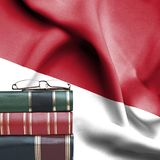 Education concept - Stack of books and reading glasses against National flag of Indonesia royalty free stock photography