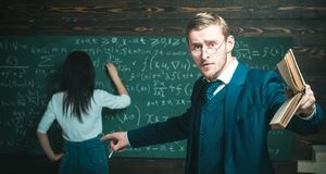 Education concept. Education of surprised teacher man point finger at woman student doing sums on chalkboard stock photography