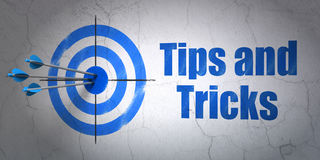 Education concept: target and Tips And Tricks on wall background. Success Education concept: arrows hitting the center of target, Blue Tips And Tricks on wall Royalty Free Stock Image