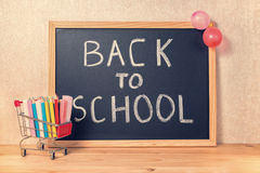 education concept with text back to school is written in chalkboard, shopping cart, pens, colorful chalks and balloons on wooden