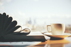 Education concept. Windowsill with open book, coffee cup and business sketch. Blurry city background with sunlight. Education concept Stock Photos