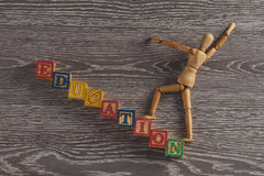 Education concept. Wooden figurine on stairs made of wooden cubes with letters Stock Photography