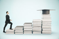 Education concept. Young businessman climbing creative book ladder with graduation cap on top. Blue background. Education concept. 3D Rendering Royalty Free Stock Images
