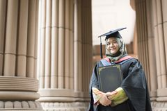 Young Malaysian woman holding a degree certificate while smiling on her graduation day. Education concept - young woman holding a degree certificate while Royalty Free Stock Images